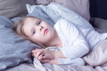 Porter of a little girl with blond hair. The baby is in its bed. Stock Photo