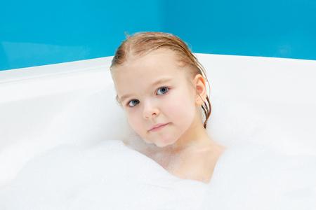 Little girl is taking a bubble bath. Portrait of a cute baby.