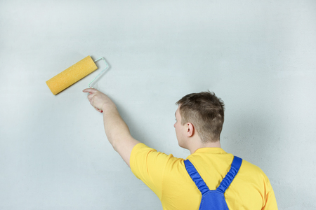 A man treats a wall with a primer using a roller. Worker makes repair. Light photo. Standard-Bild - 117900876