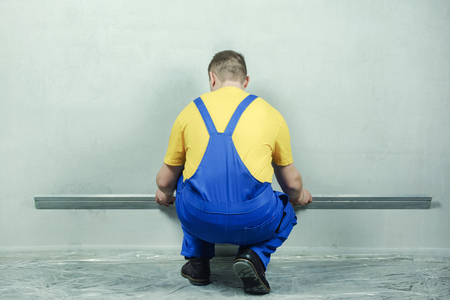 Repairman in blue jumpsuit and yellow t-shirt smooths the walls with the help of the rule. Standard-Bild - 117900908