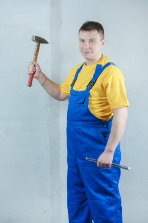 A man in a blue jumpsuit is holding a hammer and a chisel. Archivio Fotografico