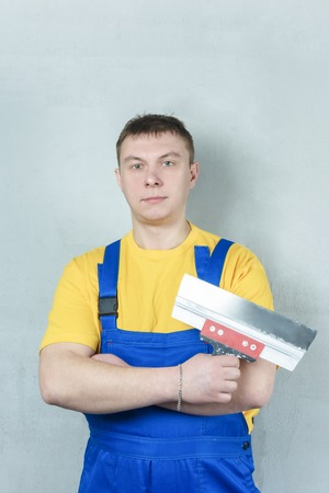 A man in a yellow T-shirt and blue overalls folded his arms across his chest. Repairman holds a spatula in his hand.
