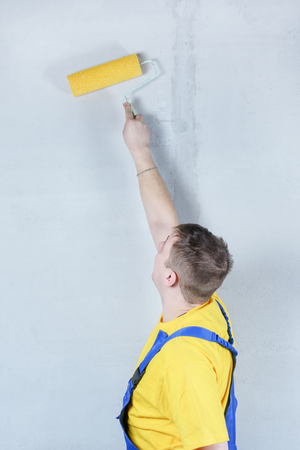 A man in a blue jumpsuit and a yellow T-shirt works with a roller. House painter covers the walls with mortar.