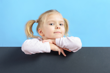 A little girl with a hair two tails. Cute baby with blond hair. Bottom on a black cardboard sheet, a place for text or an inscription.