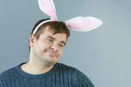 Unshaven man with bunny ears on a gray background. Faddish man is smiling.