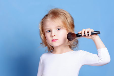 The little girl is powdered with a makeup brush. Beautiful baby with blond hair. Bright advertising photography.