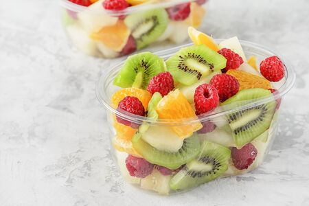 Fresh Sliced Tropical Fruits Berries in Container. Delicious Healthy Snack Ready to Eat Salad in Transparent Cup Closeup Elevated View. Vegetarian Raw Food. Citrus, Kiwi, Raspberries for Lunch