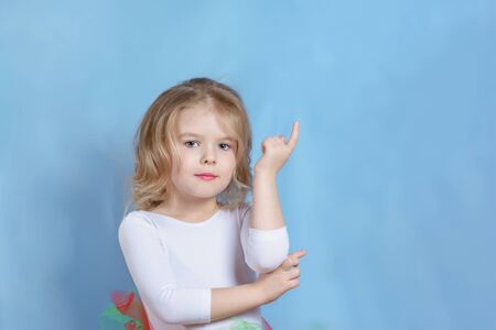 Little Caucasian Blond Girl Model Studio Head shot. Adorable Child with Short Hair Looking at Camera. Pretty Female Kid Reach out Hand with Forefinger Posing on Neutral Background Medium Shot