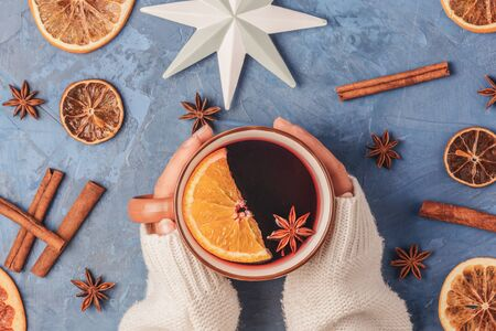 Girl Hands in Sweater Holding Cup with Mulled Wine with Spices and Orange Fruit
