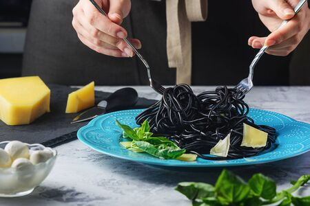 Spaghetti with Cuttlefish Black Ink and Parmesan Decorated Basil Green Leaves.