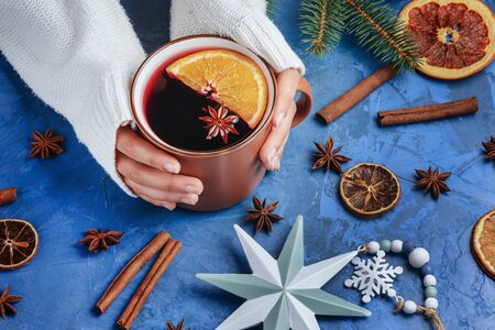 Girl Hands Holding Cup with Warming Mulled Wine with Cinnamon, Anise and Orange Fruit Photo.