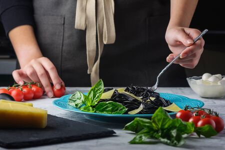 Girl Ready for Eating Italian Black Spaghetti. Exotic Cuttlefish Ink Pasta with Basil Leaves and Slices Parmesan. Imagens