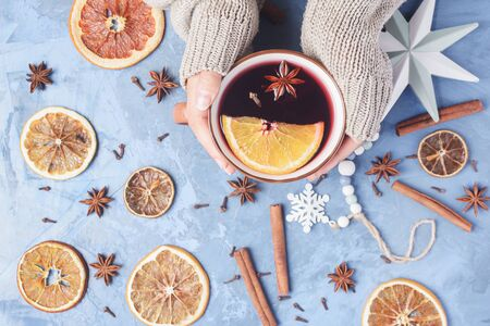 Female Hands Holding Cup Aromatic Mulled Wine with Spices and Orange Slices