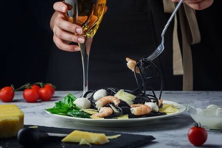 Italian Cuttlefish Black Ink Spaghetti with Prawn, Parmesan, Mozzarella and Spinach Green Leaves.