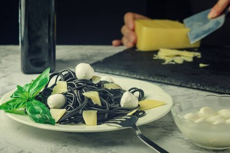 Black spaghetti with cuttlefish ink. Fancy pasta with parmesan and mozzarella. Tasty dinner.