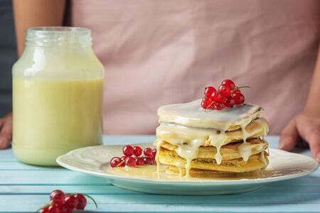 Pancakes with condensed milk. Tasty breakfast with red currant berries.
