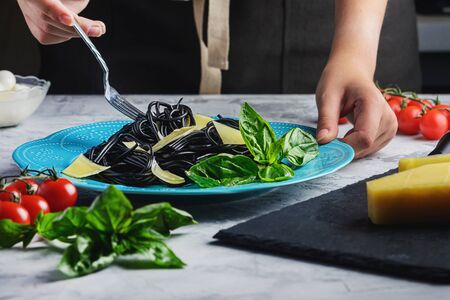 Cuttlefish Black Ink Spaghetti Italian Nutrition Decorated Basil and Parmesan. Imagens