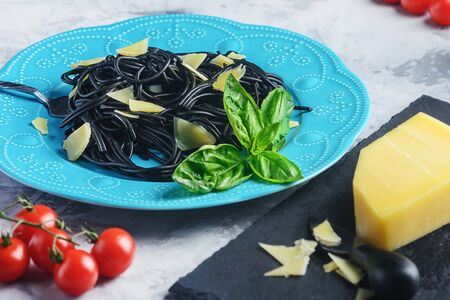Black pasta with cherry tomatoes, parmesan and basil.