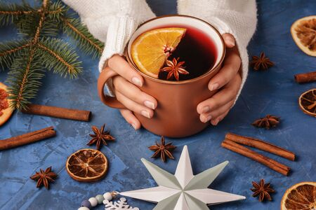 Female Hands Holding Cup with Warming Mulled Wine with Cinnamon Stick, Anise and Sliced Orange Photo. Warm Alcohol Cocktail Decorated Pine Branch and Toy in Star and Snow Shape Winter Holiday Elements