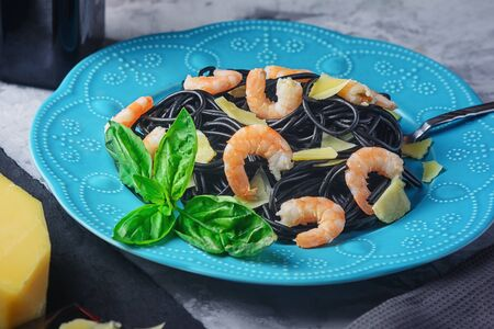 Black spaghetti on a blue plate. Unusual pasta with shrimp and parmesan. Tasty dinner.