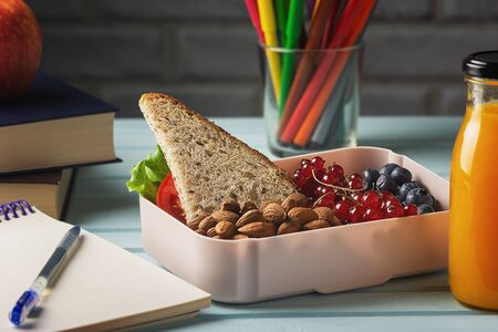 Healthy Eco Vegetarian Food in Plastic Container Copyspace. Piece of Bread with Vegetables, Currant, Blackberry and Nuts, Carrot Fresh Juice, Pen on Notebook and Multicolored Pencils on Blue Table