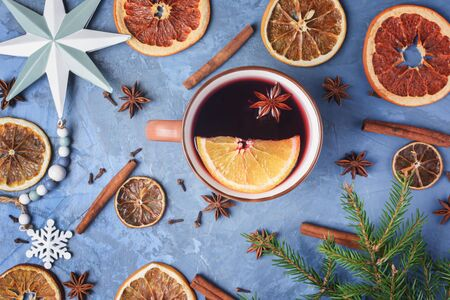 Cup Of Warm Wine with Spices and Citrus Fruit Top View Copyspace Photo. Seasonal Mug Hot Alcoholic Drink Decorated Ingredients Cinnamon and Anise, Holiday Elements Branch and Toy on Blue Background