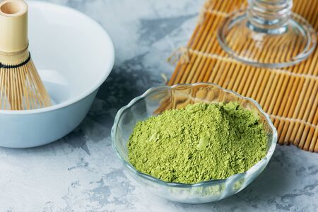 Ingredients for making matcha green tea. Powdered green tea, whisk and bowl. Close-up photo. Banco de Imagens