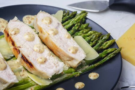Freshly prepared turkey steaks, green asparagus with peanut sauce and parmesan cheese 版權商用圖片