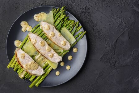 On a black  in a plate are freshly prepared turkey steaks, green asparagus with peanut sauce and parmesan cheese. 版權商用圖片