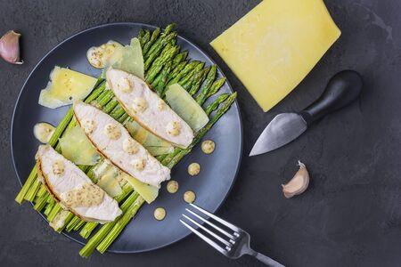 Flat lay. Turkey, asparagus and peanut sauce on a black plate.