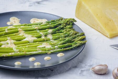 On a black plate is freshly boiled green asparagus.