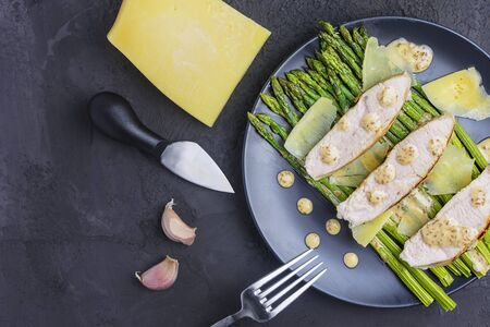 Flat with copy space. On a black plate are green asparagus, sliced turkey with peanut sauce and parmesan cheese. A healthy diet dish.