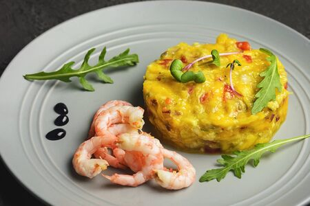 On a black background, a gray plate with an Asian national recipe. Mango chutney with pepper and shrimp. 版權商用圖片