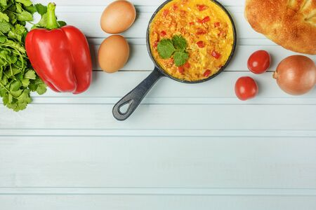 Above the blue background is a pan with Turkish national omelet and ingredients for its preparation. Mixed eggs with tomato, onion and pepper, Menemen. Flat lay with copy space.