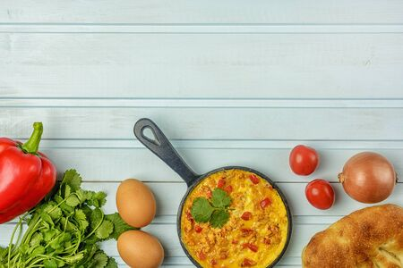 Bottom on a blue background pan with a Turkish national recipe. Omelet made from eggs, tomato, onion and pepper, Menemen. Flat lay with copy space.