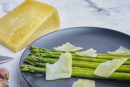On a black plate is freshly cooked green asparagus.