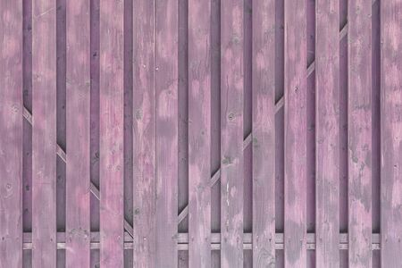 A fragment of a painted wooden gate. The structure of the boards and battens. Light purple surround background for layouts.