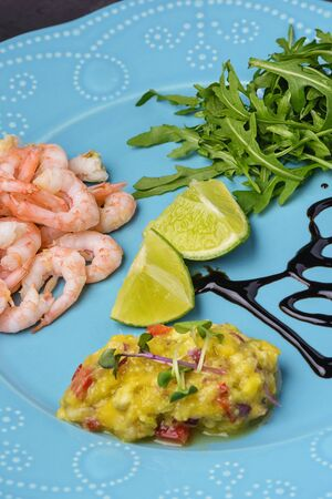 Asian mango chutney sauce, close-up. Tasty exotic dish. Shrimp on a blue plate.