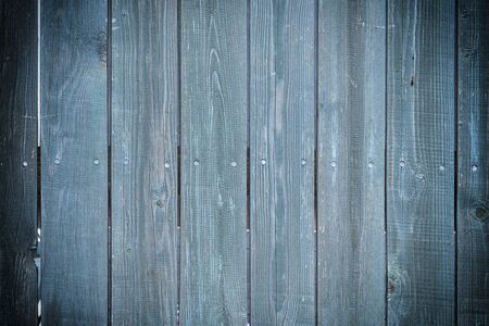 Toned photo of an old fence made of nailed boards. Dark blue background for sites and layouts with vignette.