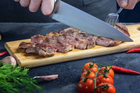 A male cook cuts a steak into portions. Fresh meat is medium rare.