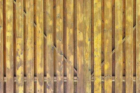 A fragment of a painted wooden gate. The structure of the boards and battens. Dirty yellow surround background for layouts.