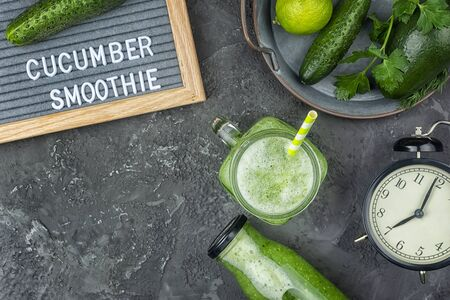 On a black background, cucumber smoothie and ingredients. Flat lay with copy space. Blackboard with the words Cucumber Smoothies. Healthy breakfast of green vegetables, vegetarianism.