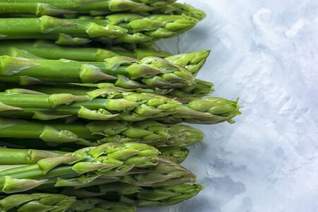 Fresh young green asparagus on a gray won.