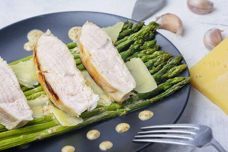 Turkey steaks with green asparagus. Tasty dinner with peanut sauce. Healthy diet food.