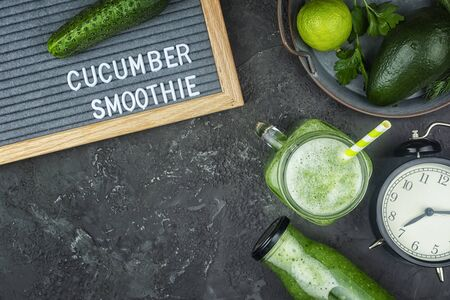 Green cucumber smoothie, cucumber juice benefits. Healthy breakfast. Vegetarian drink with avocado and herbs. Flat Lay on a black background.