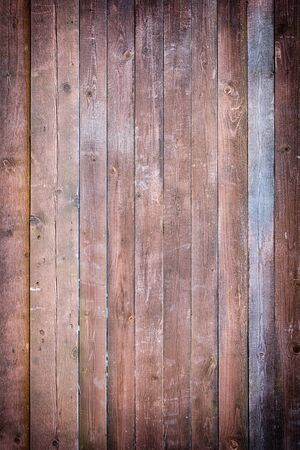 Toned photo of an old fence made of nailed boards. Dark brown background for sites and layouts with vignette.