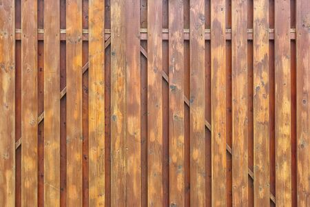 A fragment of a painted wooden gate. The structure of the boards and battens. Brown surround background for layouts.