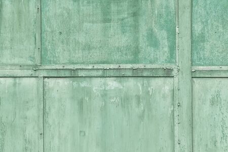 Toned photo, green background for sites and layouts. A fragment of the protective structure of metal sheets with rivets.