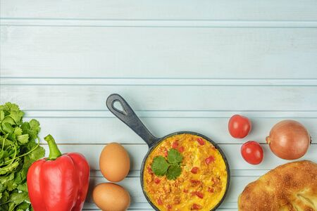 Flatlay on a blue background background. Omelet with tomatoes, onions and peppers, Menemen. Healthy breakfast. Photo with copy space. 版權商用圖片