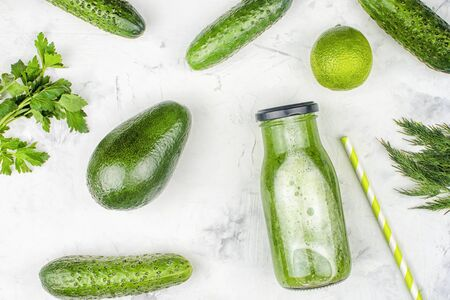 On a light background a bottle with a cucumber smoothie. Freshly squeezed cucumber juice with lime and avocado. Flat lay, ingredients.